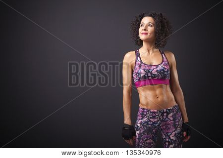 Fitness woman looking forward on dark background