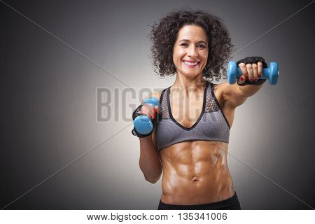 Fit woman training with dumbbells on grey bakground