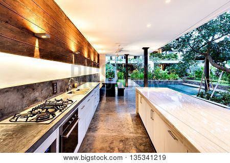 Outdoor Kitchen With A Stove An Countertop Next To Garden