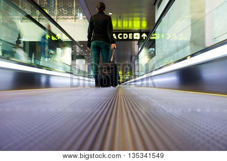 Young girl with luggage walking at airport