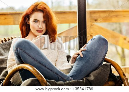 Atractive Red-haired Woman Drinking Cup Of Coffee Sitting On Roc