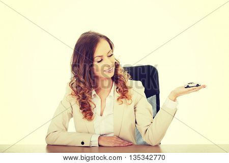 Business woman holding a toy car.