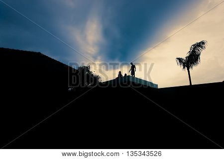 People On The Roof In A Dark Environment