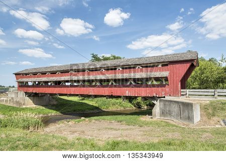 Historic red Bigelow Covered Bridge built in 1873 crosses Little Darby Creek in rural Union County Ohio.