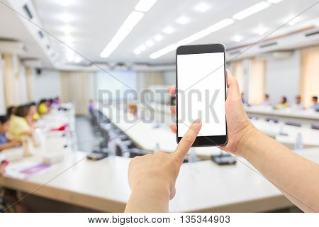 Hand using smartphone with conference room background