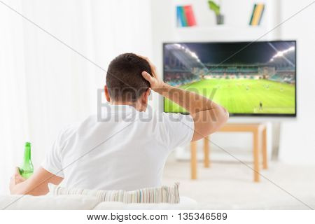 leisure, technology, sport, entertainment and people concept - man with beer bottle watching football or soccer game on tv at home