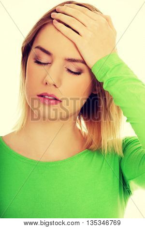 Woman with headache touching her head.