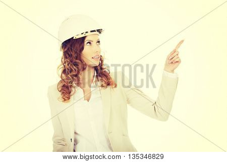 Businesswoman in white helmet pointing up.