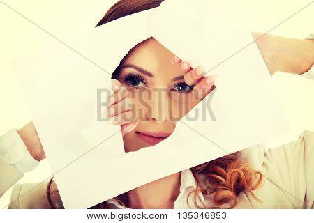 Businesswoman looking through paper sheet.