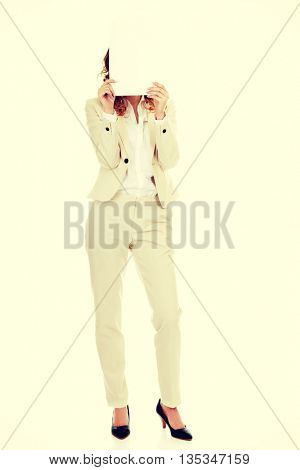 Businesswoman covering face with paper sheet.