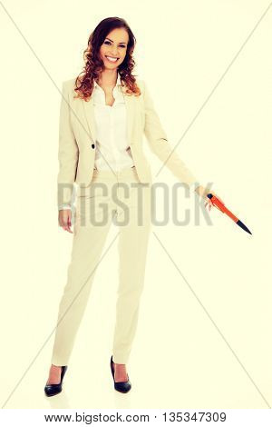 Businesswoman pointing down with pen.