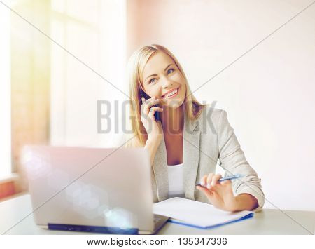 businesswoman talking on the phone and taking notes