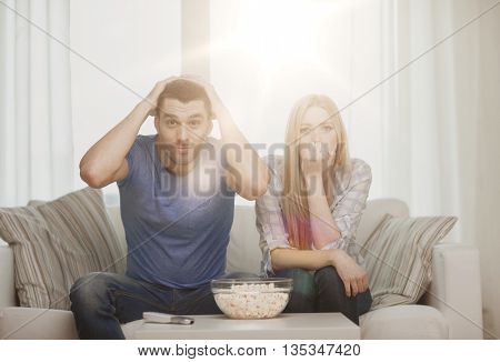 food, love, family, sports, entretainment and happiness concept - upset couple after sports team loss