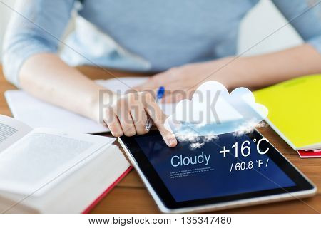 people, technology and forecast concept - close up of student woman with weather cast on tablet pc computer and notebook at home