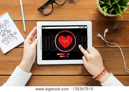 technology, people and healthcare concept - close up of woman with heart rate on tablet pc computer screen on wooden table