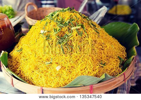 cooking, asian kitchen, sale and food concept - cooked noodles at street market