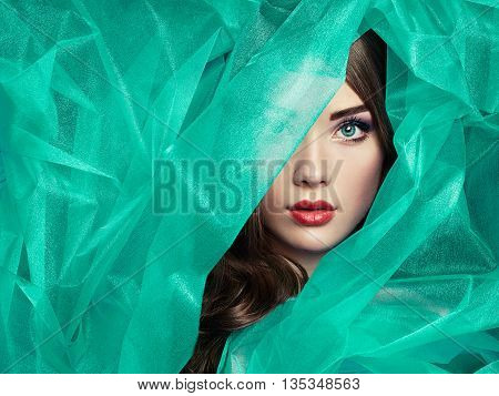 Fashion photo of beautiful women under turquoise veil. Beauty portrait. Perfect makeup. Eyelashes. Lips. Cosmetic Eyeshadow