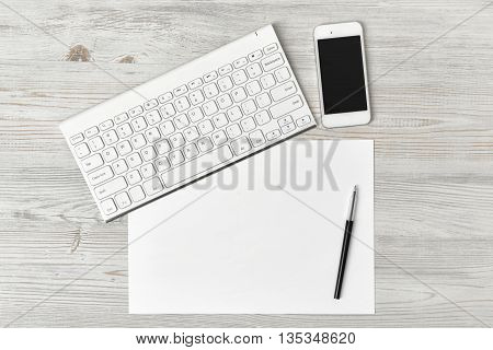 Office workplace with keyboard, pen, white blank paper and smartphone. Top view composition. Willingness to work overtime. Keeping healthy. Contribution to wellbeing. Workplace of office man.