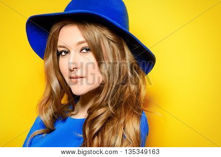 Dreamy summer girl. Smiling young woman over bright yellow background.