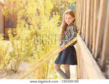beautiful little girl on stairs of wooden house on sunny day