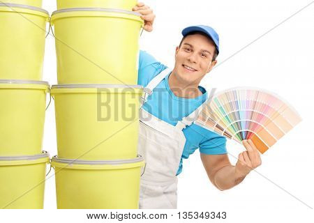 Cheerful decorator holding a color swatch and posing behind a stack of color buckets isolated on white background