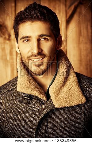 Vogue shot of a handsome male model in a coat standing by a wooden wall. Men's beauty, seasonal fashion. Toned photo, sepia.