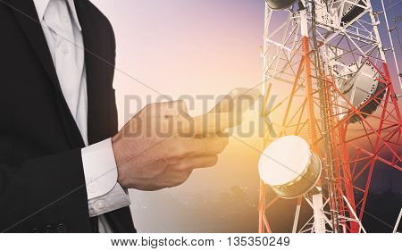 Businessman using mobile phone, with satellite dish telecom network on telecommunication tower at sunrise in rural city