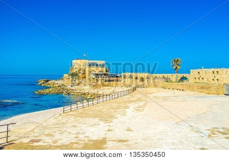 The sunny promenade of Caesaria stretches along the archaeological landmarks of the site Israel.