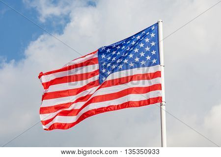 Close-up American flag with flag pole on clear blue sky background.