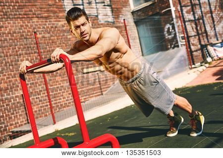 Portrait of handsome male bodybuilder doing workout outdoors.