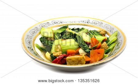 mustard fried vegetables on a plate on a white background