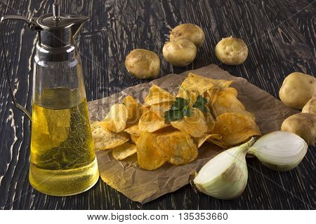 Potato chips, raw potato, onion and jug of an oil on wooden background.