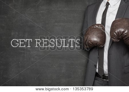 Get results on blackboard with businessman wearing boxing gloves