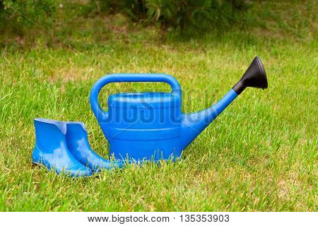 The blue plastic watering can and rubber boots on a background of green lawn. Bright equipment for garden care.