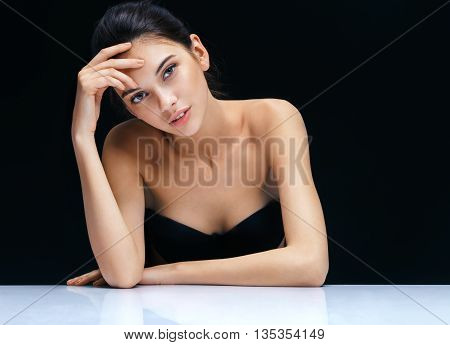 Beautiful sensual brunette girl. Close up of an attractive girl of European appearance on dark background. Skin care concept