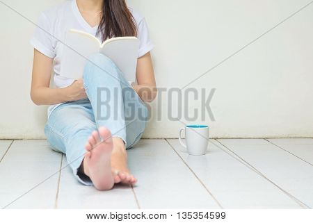Woman sitting at the corner of house for reading a book in free time in the afternoon relax time of asian woman