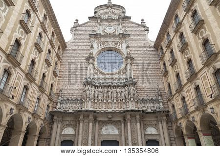 MONTSERRAT SPAIN - MAY 10 2016 : Facade of Santa Maria de Montserrat Abbey Catalonia.Santa Maria de Montserrat is a Benedictine abbey located on the mountain of Montserrat known for the cult statue of Virgin Mary.
