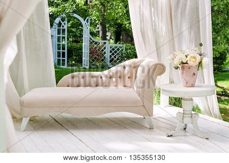 Summer garden gazebo with curtains and sofa for relaxation