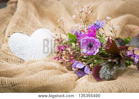 Garden style summer bouquet. Mix of lilac and purple anemone flowers, geranium flowers and heuchera or alumroot leaves. Bouquet on sackcloth background. Garden style wedding bouquet. Flower design.