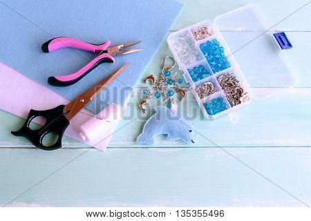 DIY keychain blue felt dolphin. Cute sea animal keychain. Simple sewing project for kids. Scissors, thread, needle, pliers, box of beads and metal pendants. Craft supplies and tools