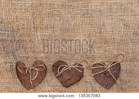 Three (3) decorative hearts made from tree bark on sackcloth, positioned under the middle of the photo. Hearts decorated with eco twine. Eco decor. St. Valentines greeting card idea. Handmade design.
