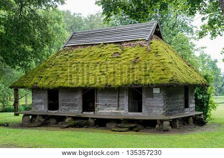The old barn with a lot of moss on the roof