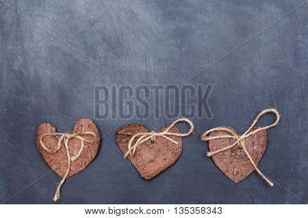 Three (3) decorative hearts made from tree bark on chalkboard, positioned under the middle of the photo. Hearts decorated with eco twine. Eco decor. St. Valentines greeting card idea. Handmade design.