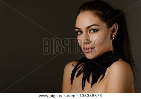 Portrait of a beautiful brunette girl with hair gathered in a ponytail with an ornament on the neck of the black feathers on dark background