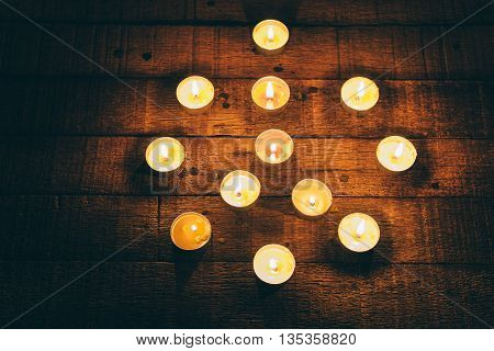 Group of lit candles in the night, represents peace sign