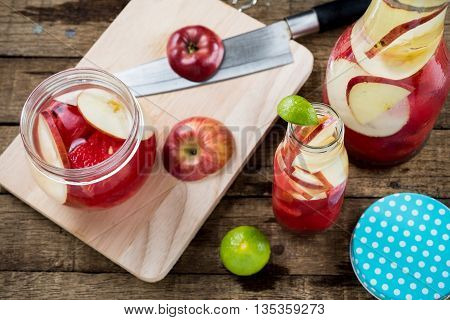 Drinks series : Infused water, watermelon and apples in glass bottles and jar on wooden plank table