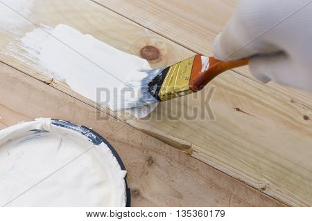 Painting timber boards outside with the white paint or white coloured emulsion using 2 inches painting brush.