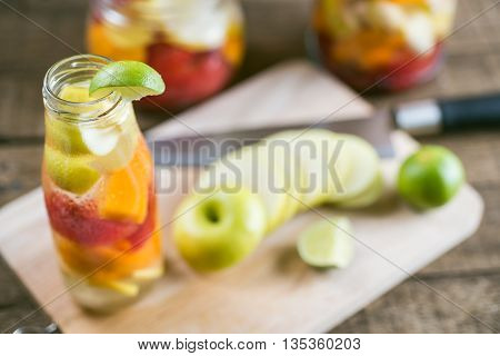 Drinks series : Infused water, watermelon, apples and mangoes in glass bottles and jar on wooden plank table, selective focus