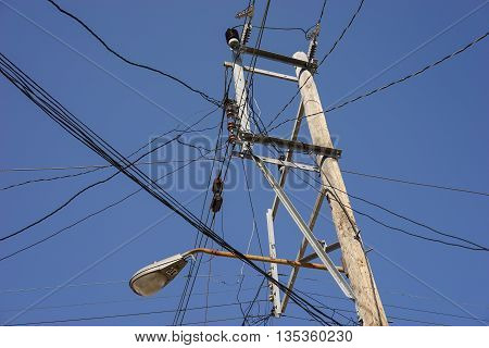 Old fashion power pole with many wires against the blue sky