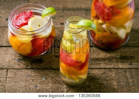 Drinks series : Infused water, watermelon, apples and mangoes in glass bottles and jar on wooden plank table
